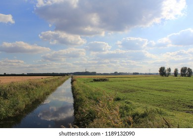 beautiful polder landscape with green meadows and a ditch and a beautiful blue sky with clouds