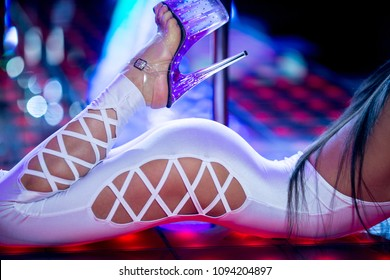 Beautiful pole dance dancer laying on the stage in the white sexy costume and high heels. Red and white lights on the background.