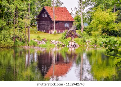 Beautiful polish, masurian lake landscape with water reflection of summer house. Mirror-like view.