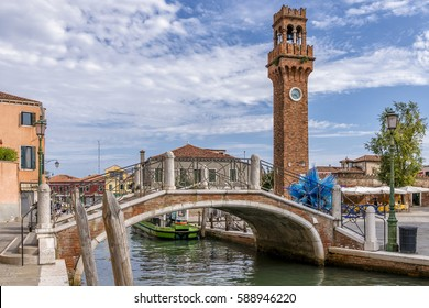 The beautiful Ponte San Pietro Martire bridge and the clock tower on the island of Murano, Venice, Italy, on a sunny day