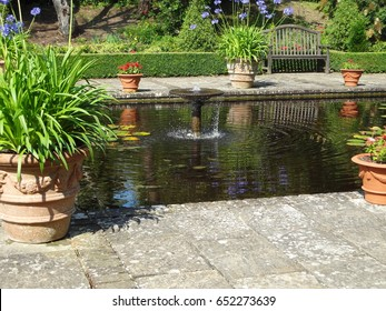 A beautiful pool surrounded by flowers and potted plants at Borde Hill Garden in West Sussex, England. United Kingdom.