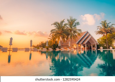 Beautiful poolside and sunset sky. Luxurious tropical beach landscape, deck chairs and loungers and water reflection. Luxurious beach chair with umbrella on private pool, ocean view