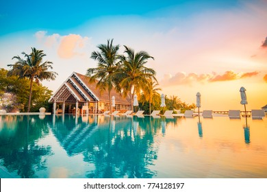Beautiful poolside and sunset sky. Luxurious tropical beach landscape, deck chairs and loungers and water reflection. - Shutterstock ID 774128197