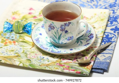 Beautiful porcelain cup with tea and candy on a napkin