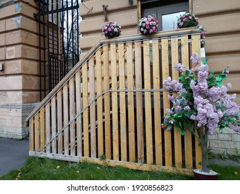 Beautiful porch with a wooden fence in and flowers at the entrance to the building