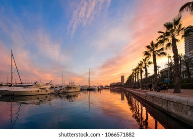 Beautiful port of Alicante, Spain at Mediterranean sea. Luxury yachts, ships, ferries and fishing boats sailing and standing in rows in harbor. Rich people traveling around the world. Sunset evening