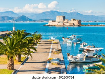 Beautiful port of Nafplio city in Greece with small boats, palm trees and Bourtzi castle on the water with selective focus