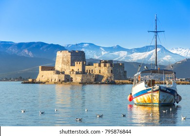 Beautiful port of Nafplio city in Greece with small boats, palm trees and Bourtzi castle on the water.