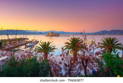 Beautiful port of Nafplio city in Greece with small boats, palm trees and Bourtzi castle on the water at sunset.