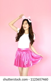 beautiful portrait Asian cheerful young girl posing in white t-shirt with pink miniskirt casual clothes with beaming smile standing isolated on pink background