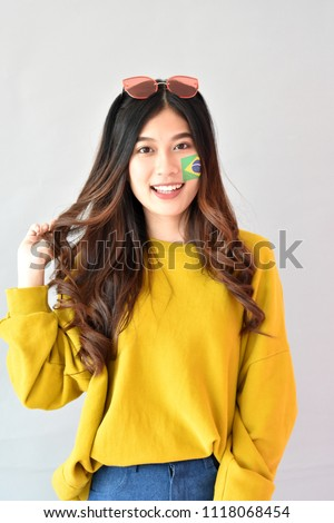 0d425779568a beautiful portrait Asian cheerful young girl posing in casual clothes. women  with the flag of Brazil makeup on face standing isolated on gray background  - ...