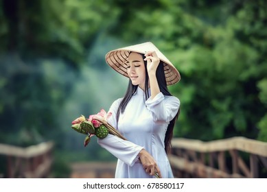 Beautiful Portrait of Asian girls with Ao-Dai Vietnam traditional dress costume woman ,Walk the bridge with Lotus, VIetnam.