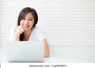 Beautiful portrait asian woman working online laptop lying on floor brick cement background, freelance girl using notebook computer with connect to internet job, business and lifestyle concept.