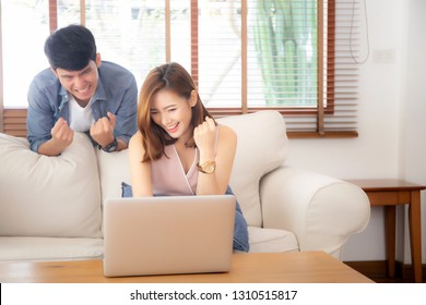 Beautiful portrait asian young couple working laptop with smile and happy sitting on couch at living room, man and woman on sofa using notebook computer with excited, business and success concept.