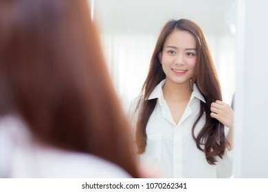 Beautiful of portrait asian young woman examining with face and smile looking on mirror at bedroom, girl beauty of makeup and dressed up with reflection, lifestyle and wellness concept.