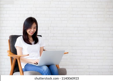 Beautiful of portrait asian young woman working online laptop sitting on chair on cement brick white background, girl using notebook computer, business concept.
