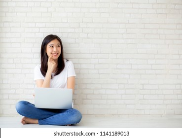 Beautiful of portrait asian young woman working online laptop and thinking sitting on floor brick cement background, freelance girl using notebook computer, business and lifestyle concept.