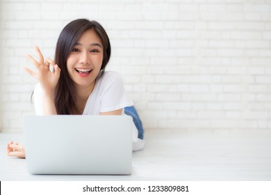 Beautiful portrait asian young woman working online laptop with excited lying on floor brick cement background, freelance girl smile using notebook computer with happy, business and lifestyle concept.