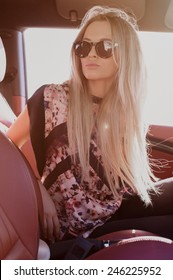 Beautiful portrait of blondie young lady at the wheel of sport car with red interior, with sunglases, natural makeup and lipstik, black top with small flowers looking at you