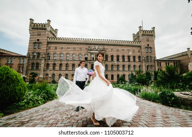 Beautiful portrait bride are dancing for groom and spinning back near ancient restored architecture, old building, old house outside, vintage palace outdoor.