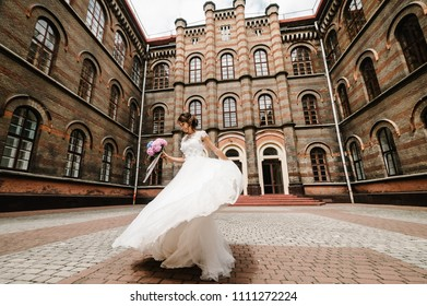 Beautiful portrait bride are dancing and spinning back near ancient restored architecture, old building, old house outside, vintage palace outdoor.