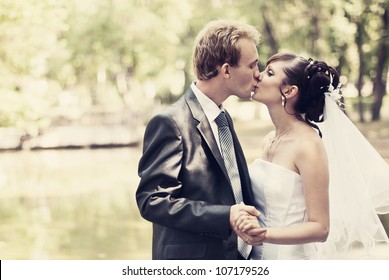 Beautiful portrait of the bride and groom kissing in the park and holding hands.