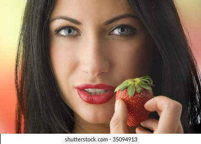 beautiful portrait of cute brunette girl with strawberry near her face