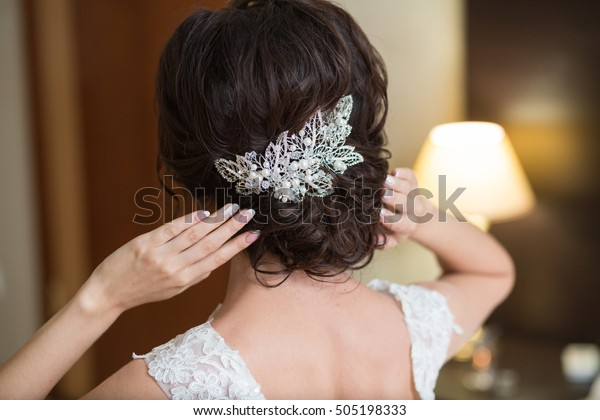 Beautiful portrait of a cute brunette gorgeous bride's hairstyle, back view. Wedding hairstyle with jewelry decoration, close up