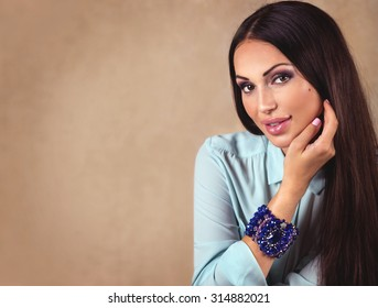 Beautiful portrait of fashion brunette model woman with long hair and luxury blue jewelry. Beige background with copy space