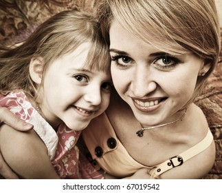 Beautiful portrait of happy cheerful mother with little daughter in embrace