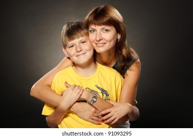 Beautiful portrait of happy cheerful mother with her son in embrace