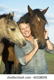 A beautiful portrait of a happy laughing man bonding with his two horses