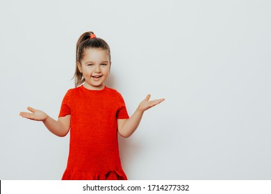 Beautiful portrait of a little girl 4-5 years old, fun smile. child girl posing in studio holding hands up, young model wears a red dress and ponytail hairstyle