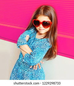 Beautiful portrait little girl child in red heart shape sunglasses on colorful pink background