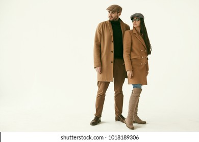 Beautiful portrait of a loving couple dressed in a yellow fashion coat isolated on white background in studio