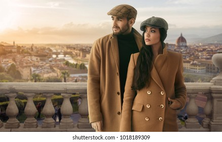 Beautiful portrait of a loving couple dressed in a yellow fashion coat on background of beautiful urban european view