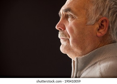 Beautiful portrait of a pensive senior man with a moustache in profile on a black background with copyspace staring straight ahead as he reminisces on his life