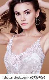 Beautiful portrait pretty sexy brunette woman long curly hair organic cosmetic for face care  body hand makeup fashion beauty salon spa accessory jewelry neck earring perfect skin tan hair manicure.