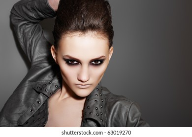 Beautiful portrait of rock woman model in leather jacket with dark evening make-up. Perfect street fashion. Personal accessories, clothes.