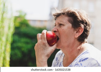 Beautiful portrait of senior woman eating red apple outside on a summer day - Cute old lady with healthy and delicious fruit in nature - Elderly person enjoying nutritious and rich in vitamin snack
