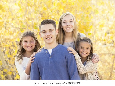 Beautiful Portrait of smiling happy kids outdoors. Four siblings standing together for a cute picture on a warm fall day