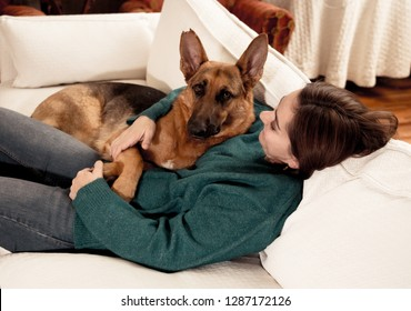 Beautiful portrait of smiling woman hugging her dog german shepherd together in front of fireplace at cozy home in winter day in happiness Friendship Love Companionship and benefits of pets animals.