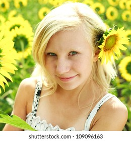 Beautiful portrait of summer young girl in the field of sunflowers