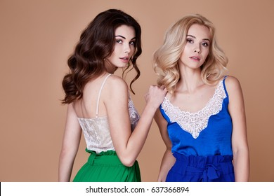 Beautiful portrait of two pretty sexy brunette blond woman long curly hair organic cosmetic for face care body hand makeup fashion beauty salon spa accessory jewelry neck earring lace top lingerie.