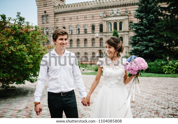 Beautiful portrait wedding couple are walking near ancient restored architecture, old building, old house outside, vintage palace outdoor. Romantic love in vintage atmosphere street.
