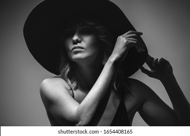 Beautiful portrait of a woman in a big hat. Studio. Close-up. The photo is black and white.