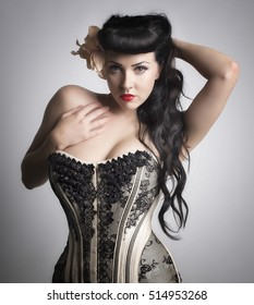 Beautiful portrait of a woman wearing black and white corset with long dark hair