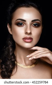 Beautiful portrait of a woman. Young girl posing on black background with gorgeous make up.
