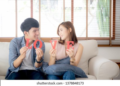 Beautiful portrait young asian couple holding word love together in living room, family husband and wife smiling with happy, man and woman lover wearing casual with relax, lifestyle co
