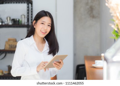 Beautiful portrait young asian woman using tablet computer in the coffee shop, businesswoman sitting looking tablet is work at cafe, communication concept.